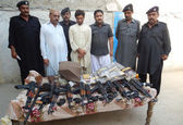 Excise Police officials are showing seized weapons and drugs that recovered during raid on a truck moving to Karachi from Peshawar, at Ubauro — Stock Photo