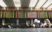 Pakistani traders sit beneath an electronic display board showing the ongoing development of various stock shares at the Karachi Stock Exchange (KSE) — Stock Photo
