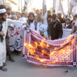 Activists of Jamat-ud-Dawah burn the US flag as they are protesting drone attacks by U.S Army and killing of innocent citizens of Pakistan in these attacks — Stock Photo