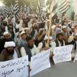 Постер, плакат: Activists of Jamiat Ulema Islam Nazaryati chant slogans against sectarian clashes in Rawalpindi on Ashura procession