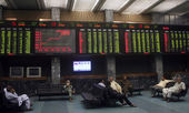 Traders sit beneath an electronic display board showing the ongoing development of various stock shares at the Karachi Stock Exchange (KSE) — Stock Photo
