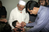 Deputy Commissioner West, Ghulam Qadir Talpur administrating anti polio vaccines to children during a campaign held at Kunwari colony area — Stock Photo