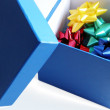 Blue gift box with ribbon flowers — Stock Photo #25112927