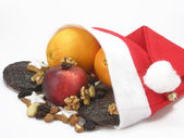 Christmas Gifts - Christmas hat containing fruits and sweets — Stock Photo