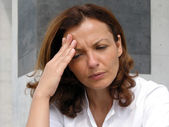 Sadness - Woman is sad and rubs his forehead — Stock Photo