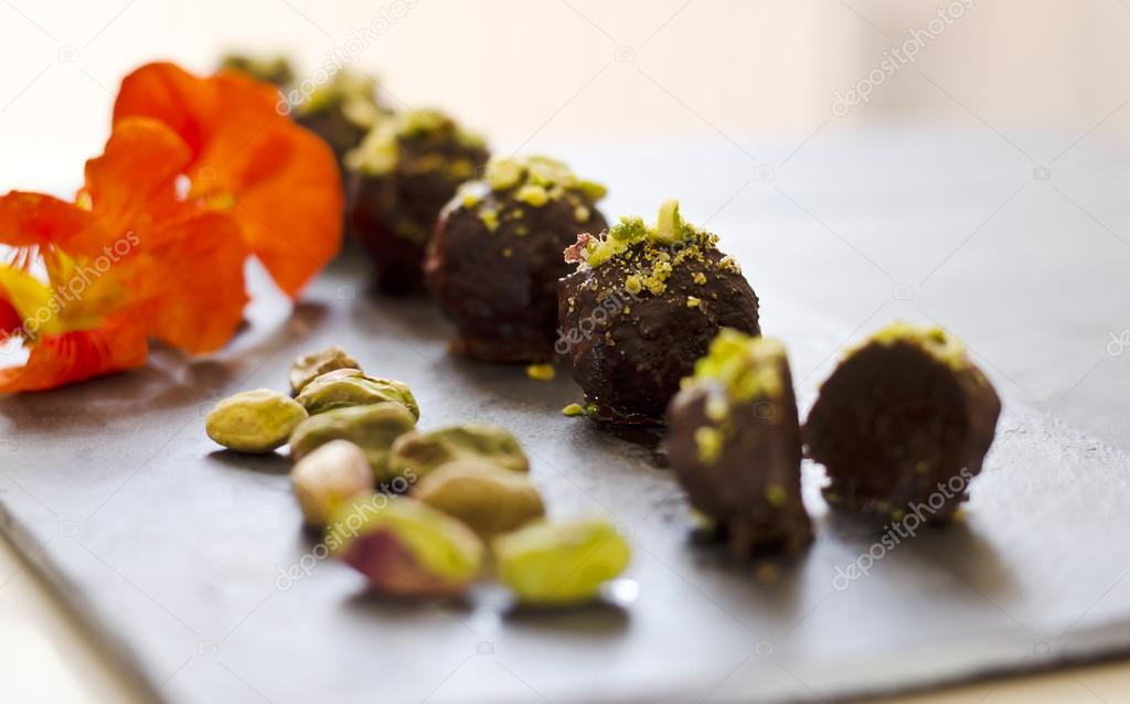 Raw food chocolate pralines on a dark plate with decoration — Stock Photo #12574497