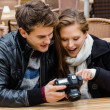 Couple Looking At Photographs On Digital Camera At Restaurant — Stock Photo