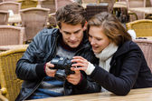 Couple Looking At Photographs On Camera At Restaurant — Stock Photo