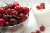 Skål med körsbär och yoghurt med hallon — Stockfoto