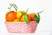 Roze mand met mandarijnen — Stockfoto
