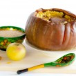 Foto de Stock  : Hole baked pumpkin and wooden bowl with spoon with Khokhlompainting