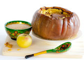 Hole baked pumpkin and wooden bowl with a spoon with the Khokhloma painting — Stok fotoğraf