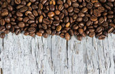 Coffee beans on the old wood — Stock Photo