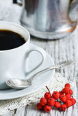 Cup of coffee and red rowan berries — Stock Photo
