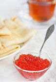 Red caviar, pancakes and cup of tea — Stock Photo