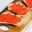 Red caviar on a slice of bread and butter — Stock Photo #13310441