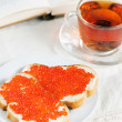 Red caviar on a slice of bread, tea and open book — Stock Photo #13433365