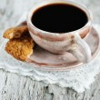 Cup of coffee and broken cookie - Stock Photo