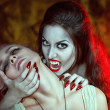 Beautiful vampire and her victim — Stock Photo #30878139