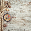 Ship rope, shells, compass and wood background — Stock Photo