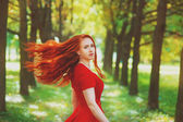Beautiful woman with red fluttering hair — Stock Photo