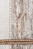 Linen fabric with lace and rope on the old wood — Stock Photo