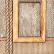 Wooden frame on the burlap with sacking ribbon and rope — Stock Photo