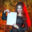 Halloween vampire holding sheet of paper — Stock Photo