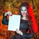 Halloween vampire holding sheet of paper — Stock Photo