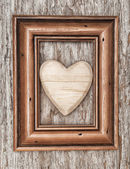 Wooden heart in frame on the old wood — Stok fotoğraf