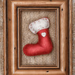 Red sock with burlap textile and wooden frame on the old wood — Stock Photo
