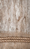 Rope and burlap textile on the old wood — Stock Photo