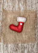 Red sock with the burlap textile on the old wood — Stok fotoğraf