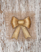 Golden bow on the burlap textile and old wood — Stok fotoğraf