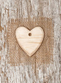 Wooden heart with burlap textile on the old wood — Stock fotografie