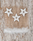Star shapes and burlap textile on the old wood — Foto Stock