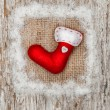 Red sock with burlap textile and snow — Stock Photo