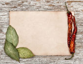 Aged sheet of paper with dry bay leaves and pepper — Stock Photo