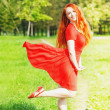 Redhead woman with red fluttering dress — Stock Photo