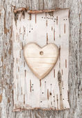 Wooden heart with birch bark on the old wood — Stock Photo
