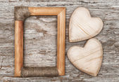Wooden hearts and frame on the old wood — Stock Photo