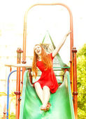 Happy redhead woman on a children slide — Stock Photo
