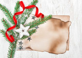 Christmas card with aged paper, stars and fir branches — Stock Photo