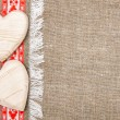 Burlap background bordered by country cloth and wooden hearts — Stok fotoğraf