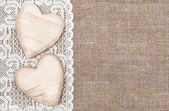 Burlap background with lacy cloth and wooden hearts — Fotografia Stock