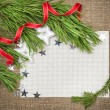 Christmas card with fir branch, stars and red ribbon on burlap — Foto Stock