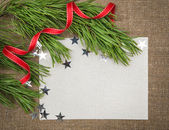 Christmas card with fir branch, stars and red ribbon on burlap — Stock Photo