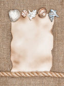 Aged paper with sea shells and rope on sacking background — Stock Photo