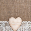 Burlap background with lacy cloth and wooden heart — Stock Photo