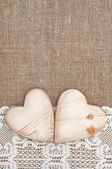 Burlap background with lacy cloth and wooden hearts — Stock Photo